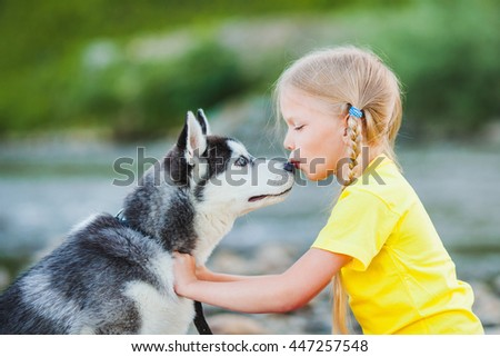 Little girl kissing puppy Huskies - stock photo