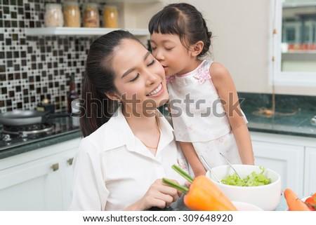 little girl kissing their mother - stock photo