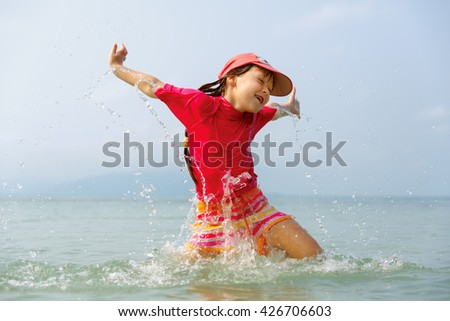 Little girl laughing and crying in the spray of waves at sea on a sunny day