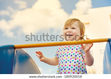 Little girl laughing on the playground - stock photo