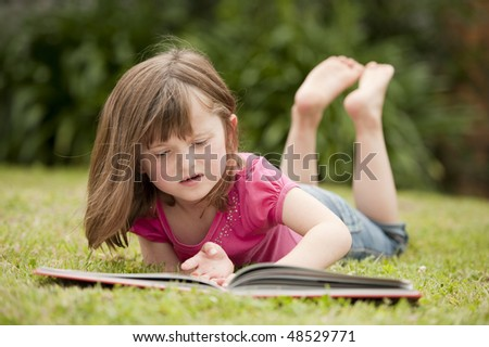 little girl laying in grass and reading