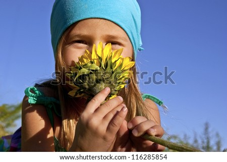 Little girl laying in grass and smelling a sunflower - stock photo