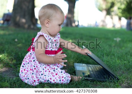 Little girl laying on grass with laptop in summer park