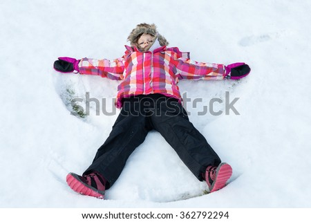 Little girl laying on snow and making - Snow Angel. Child smiling and spreading hands and feet - winter fun - stock photo