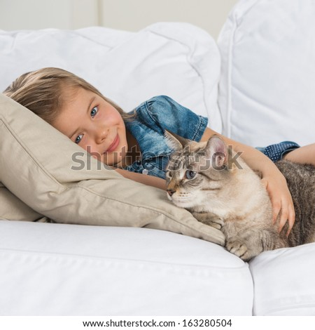Little girl laying on sofa with her tabby cat - stock photo