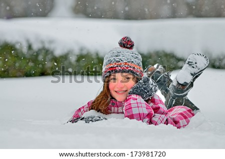 little girl laying on the snow - stock photo