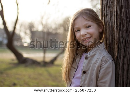 Little Girl leaning against a tree in the park, with a smile on her face looking at the camera.