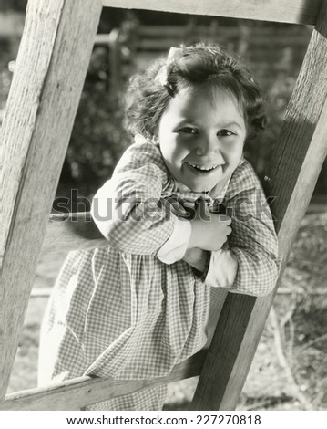 Little girl leaning on ladder - stock photo