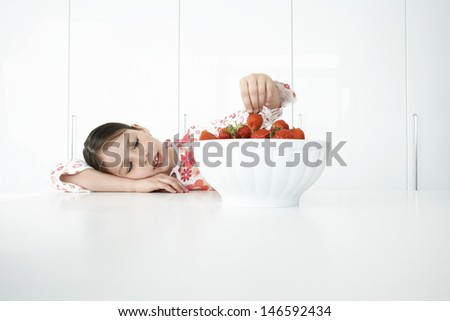 Little girl leaning on table and picking strawberries from bowl - stock photo