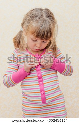 Little girl learning buttoning her striped pajama.
