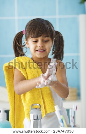 Little girl learning good habit washing hands, protecting from germs - stock photo