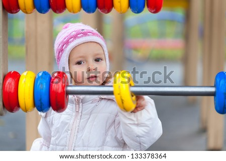 Little girl learning to count in the autumn park - stock photo