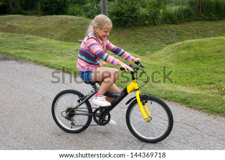 little girl learning to ride a bicycle on empty street - stock photo