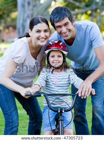Little girl learning to ride a bike with her parents in a park - stock photo