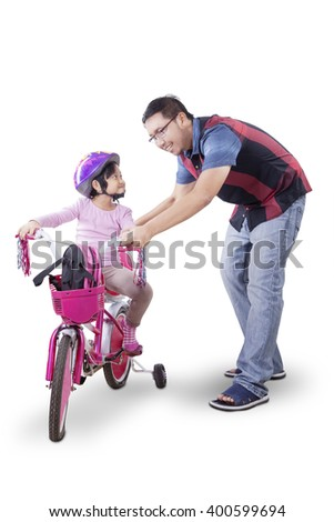 Little girl learning to ride bicycle with her father in the studio, isolated on white background - stock photo