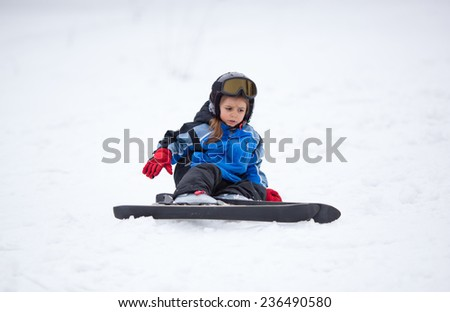 Little girl learning to ski just fell on snow - stock photo