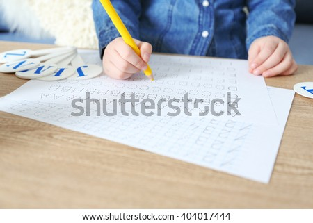 Little girl learning to write English letters at the table - stock photo