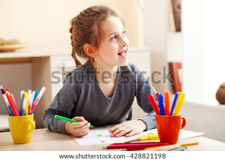 Little girl learns to draw.She uses colored pencils. - stock photo