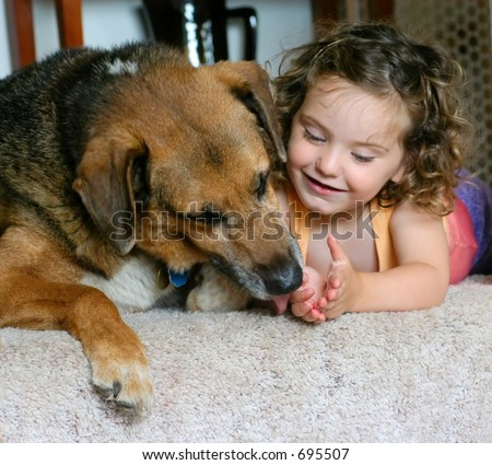 Little girl lets her dog lick her hand at the top of the stairs - stock photo