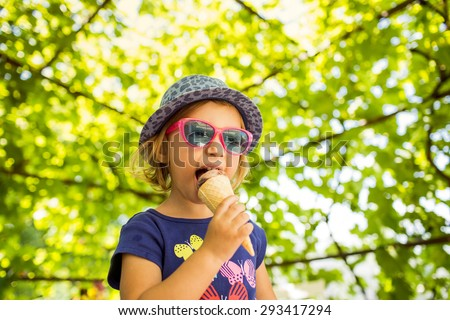 little girl  licking ice cream in a cone - stock photo