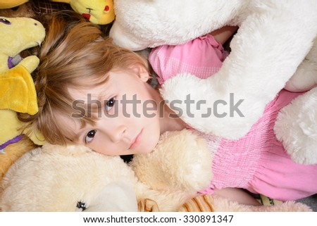 Little girl lies among stuffed toys and smiling