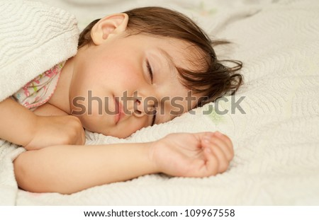 Little girl lies in bed on a white background