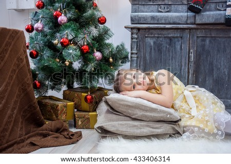 little girl lies on pillows in a yellow dress, Christmas - stock photo