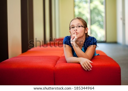 Little girl lifestyle shot in  a sunny room with her finger to her lips asking for quiet or silence laying on a red couch with an out of focus background and  room for copy - stock photo