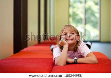Little girl lifestyle shot in  a sunny room with her hand on her face laying on a red couch with an out of focus background and  room for copy - stock photo
