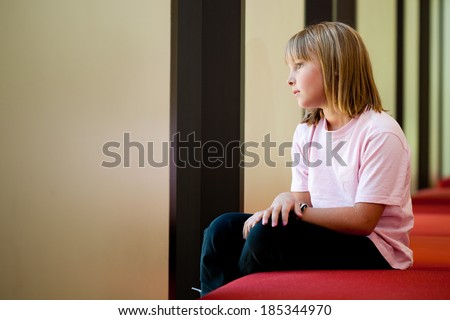 Little girl lifestyle shot sitting on a red bench looking out a window daydreaming  in a sunny room with her arms folded with an out of focus background and  room for copy
