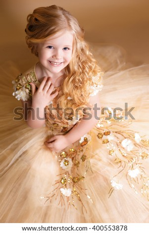 little girl like a doll with curly golden hair in nice gold dress. little fairy princess - stock photo