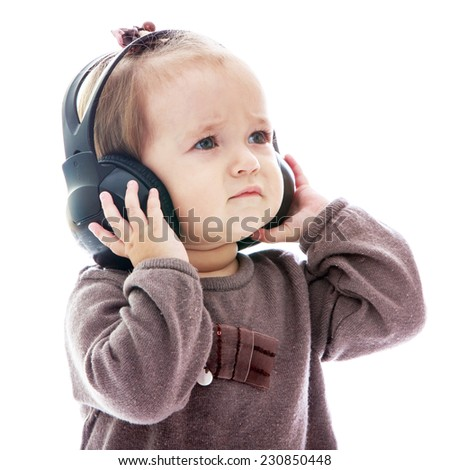 Little girl listening to classical music in big black headphones.Isolated on white background. - stock photo