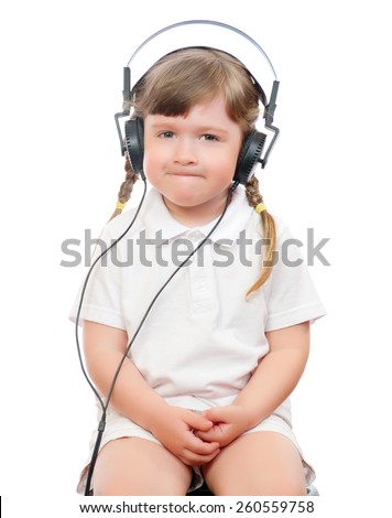 little girl listens music in ear-phones - stock photo