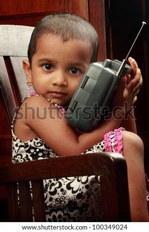 Little girl listens to radio - stock photo