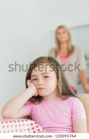 Little girl looking annoyed sitting at kitchen table with mother in background - stock photo