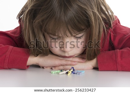 Little girl looking at a small colored keys  isolated on white background