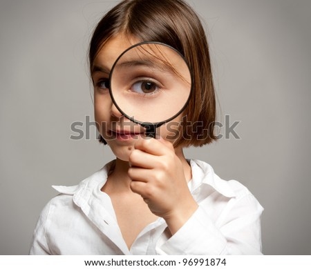 little girl looking at camera through magnifying glass - stock photo