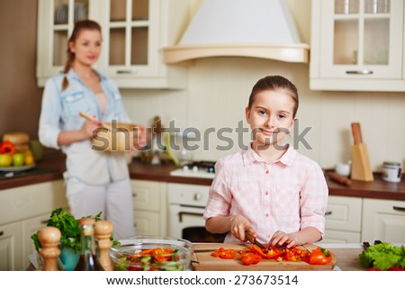 Little girl looking at camera while cutting pepper with her mother on background - stock photo