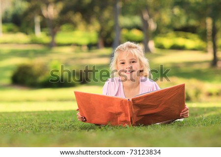 Little girl looking at her album photo - stock photo