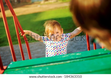 Little girl looking at her mother playing on the street - stock photo