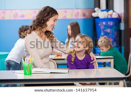 Little girl looking at kindergarten teacher with students in background - stock photo