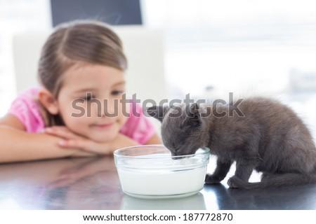 Little girl looking at kitten drinking milk from bowl - stock photo
