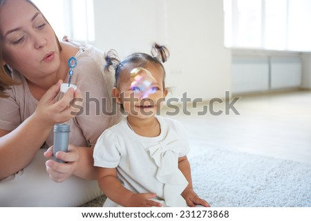 Little girl looking at soap bubbles blown by her mother - stock photo
