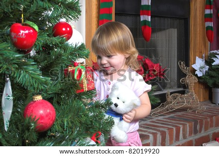 Little girl looking at the ornaments on christmas tree