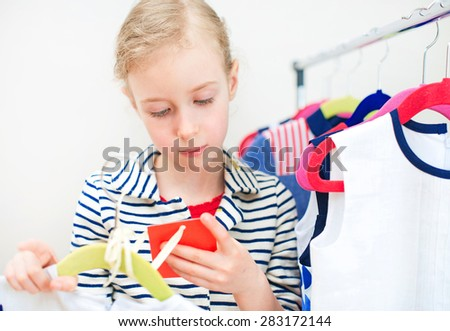 Little girl looking at the price label in clothing store. - stock photo