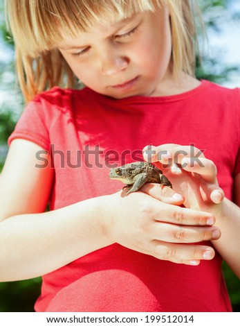 Little girl looking at true toad sitting on her hand - stock photo
