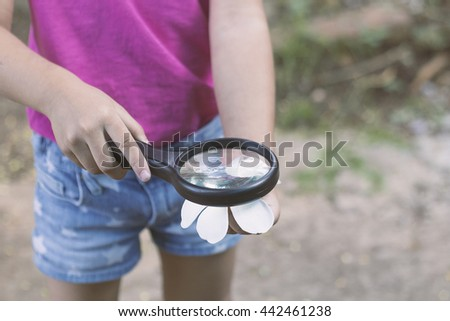 little girl looking Flower through magnifying glass. Vintage style filtered photo