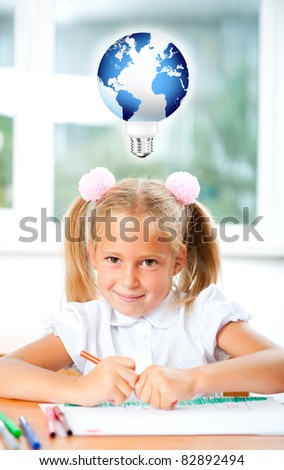 Little girl looking for a drawing concept wile painting picture on paper sheet. Indoors at classroom. Vertical Shot. Earth with lamp shape near her head - idea symbol. - stock photo