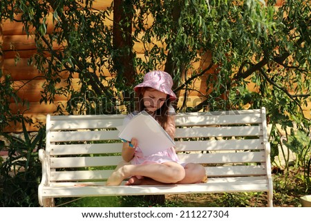 Little girl looking her album for drawing sitting in the summer park bench - stock photo