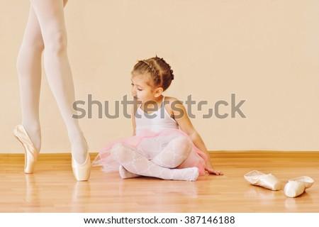 little girl looking on feet of trainer in ballet school - stock photo